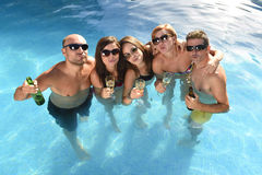 Happy attractive men and women in bikini having bath at hotel resort swimming pool drinking beer Royalty Free Stock Image