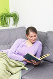 Happy woman reading a book Stock Photos