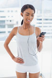 Happy attractive model in sportswear listening to music Royalty Free Stock Photos