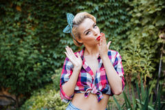 Happy attractive pinup girl sending a kiss in the garden Royalty Free Stock Image