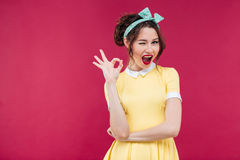Happy attractive pinup girl in yellow dress showing ok sign Stock Image