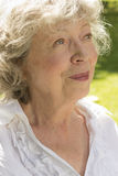 Happy and attractive retired woman, portrait. Face of a happy and attractive retired woman outdoors, close-up Stock Image