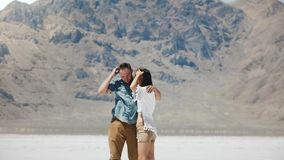 Happy attractive romantic couple stand together hugging, kissing at epic white flat salt desert of Bonneville Utah. stock video