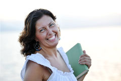 Happy attractive 40s mature woman holding book smi Royalty Free Stock Image