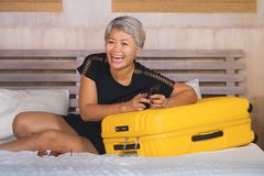 Happy and attractive 40s to 50s mature Asian tourist woman with grey hair arriving in holiday hotel room excited on bed joyful. Travel bliss . natural lifestyle stock images