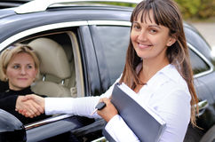 Happy attractive saleslady finalising a deal. Shaking hands with a blond women who has just purchased a new car from her Royalty Free Stock Image