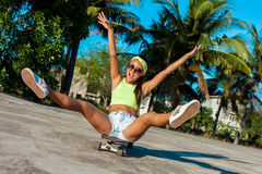 Happy attractive young woman in sunglasses sitting on skateboard near palms in park.