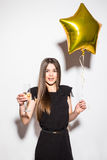 Happy attractive shocked young woman in black dress holding star shaped balloon and drinking champagne Royalty Free Stock Photos