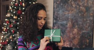 Happy Attractive Smiling Mulatto Girl, Holding Nice Wraped Christmas Present in her Hands, Correcting Bow, Standing near. Christmas Tree. Christmas and New Year stock video
