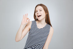 Happy attractive teenage girl in striped top showing ok sign Royalty Free Stock Image