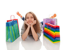 The happy customer. The happy attractive teenager girl lying with bags for purchases on a white background Stock Photos