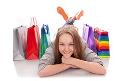 The happy customer. The happy attractive teenager girl lying with bags for purchases on a white background Stock Photo