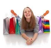 The happy customer. The happy attractive teenager girl lying with bags for purchases on a white background Royalty Free Stock Images