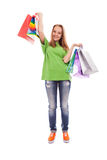 The happy customer. The happy attractive teenager girl standing with bags for purchases on a white background royalty free stock image