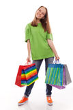 The happy customer. The happy attractive teenager girl standing with bags for purchases on a white background Royalty Free Stock Photography