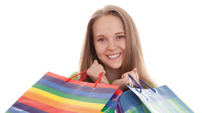 The happy customer. The happy attractive teenager girl standing with bags for purchases on a white background Stock Image