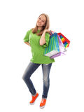 The happy customer. The happy attractive teenager girl standing with bags for purchases on a white background Royalty Free Stock Photo