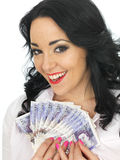 Happy Attractive Wealthy Young Woman Holding Money. Happy Attractive wealthy Young Woman with long black curly hair and hispanic or european features, looking at Royalty Free Stock Images