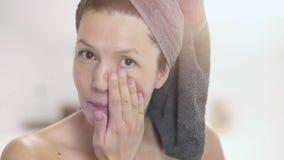 Happy attractive woman applying face cream stock video footage