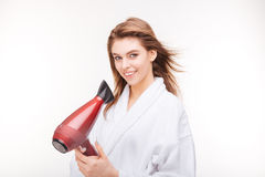 Happy attractive woman in bathrobe standing and using hair dryer. Happy attractive young woman in bathrobe  standing and using hair dryer over white background Royalty Free Stock Image