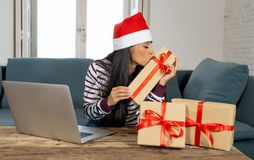 Happy attractive woman buying christmas presents online looking excited with gifts stock photography
