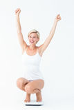 Happy attractive woman crouching on a scales Royalty Free Stock Image