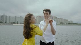 Happy attractive woman dancing with her boyfriend at the embankment in the city stock video