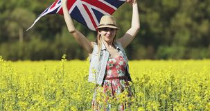 A happy attractive woman with the English flag is dancing in a yellow rapeseed field in summer. Female model is waving flag of Great Britain in the wind and stock footage