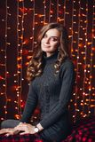 Happy attractive woman in gray knit dress against Christmas lights. royalty free stock image