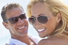 Happy Attractive Woman and Man Couple At Beach. A happy and attractive man and woman couple wearing sunglasses and smiling in sunshine at the beach Stock Photos