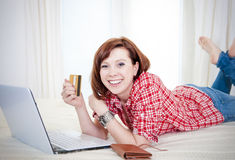 Happy attractive woman online shopping. Happy attractive red haired  woman wearing a red shirt  lying on her bed on her laptop online shopping on white Royalty Free Stock Photo