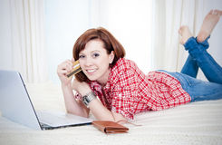 Happy attractive woman online shopping. Happy attractive red haired  woman wearing a red shirt  lying on her bed on her laptop online shopping on white Royalty Free Stock Images