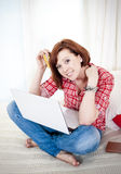 Happy attractive woman online shopping. Happy attractive red haired  woman wearing a red shirt  lying on her bed on her laptop online shopping on white Stock Photo