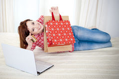Happy attractive woman online shopping. Happy attractive red haired  woman wearing a red shirt  lying on her bed on her laptop online shopping on white Royalty Free Stock Photos