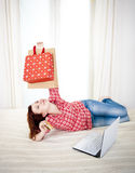 Happy attractive woman online shopping. Happy attractive red haired  woman wearing a red shirt  lying on her bed on her laptop online shopping on white Stock Photos