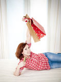 Happy attractive woman online shopping. Happy attractive red haired  woman wearing a red shirt  lying on her bed on her laptop online shopping on white Stock Image