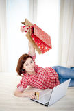 Happy attractive woman online shopping. Happy attractive red haired  woman wearing a red shirt  lying on her bed on her laptop online shopping on white Royalty Free Stock Photography