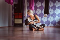 Attractive woman playing with her cute dog while sitting on floor in yoga fitness club. Happy attractive woman playing with her cute dog while sitting on floor stock photos