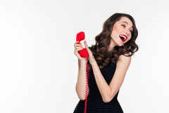 Happy attractive woman with retro hairstyle talking covering phone receiver Stock Image