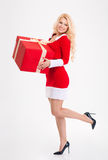 Happy attractive woman in santa claus costume with big gift Stock Images