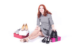 Happy attractive woman sitting on the floor and measures the shoes Royalty Free Stock Photos