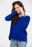 Happy attractive  woman standing and talking on mobile phone Stock Photo