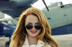 Happy attractive woman in sunglasses outside near military plane Royalty Free Stock Image