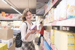 Happy, attractive woman is in the supermarket with a pack of quick breakfasts in her hands and smiles royalty free stock image
