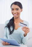 Happy attractive woman using her tablet pc to buy online Royalty Free Stock Photo