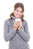 Happy attractive woman in woolen sweater and muffs holding cup o Stock Photo