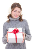 Happy attractive woman in woolen sweater and muffs holding gift Royalty Free Stock Image
