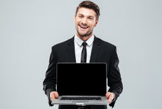 Happy attractive young businessman holding blank screen laptop Stock Photos