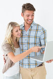 Happy attractive young couple using laptop Stock Photos