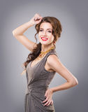 Happy, attractive, young lady posing wearing a golden necklace Royalty Free Stock Photo